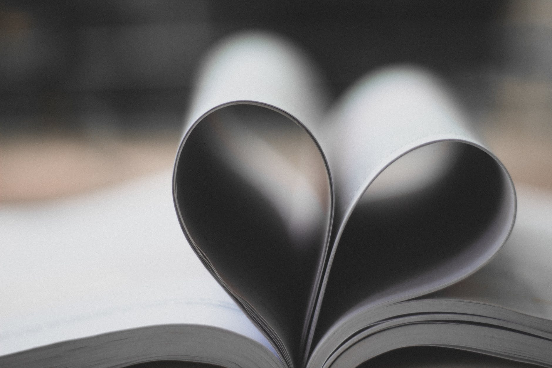 closeup photography of book page folding forming heart